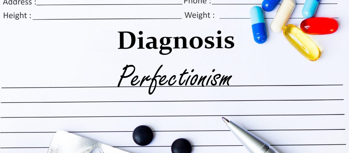 Perfectionism - Diagnosis written on a piece of white paper with medication and Pills