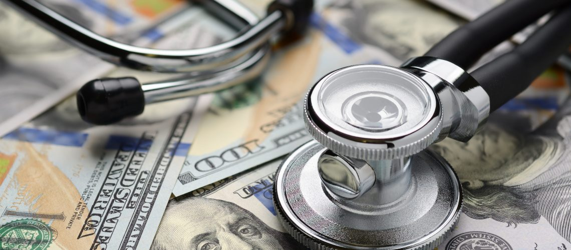 Medical stethoscope on heap of dollar bills. Health care or insurance costs concept. Finance banking audit analytics.