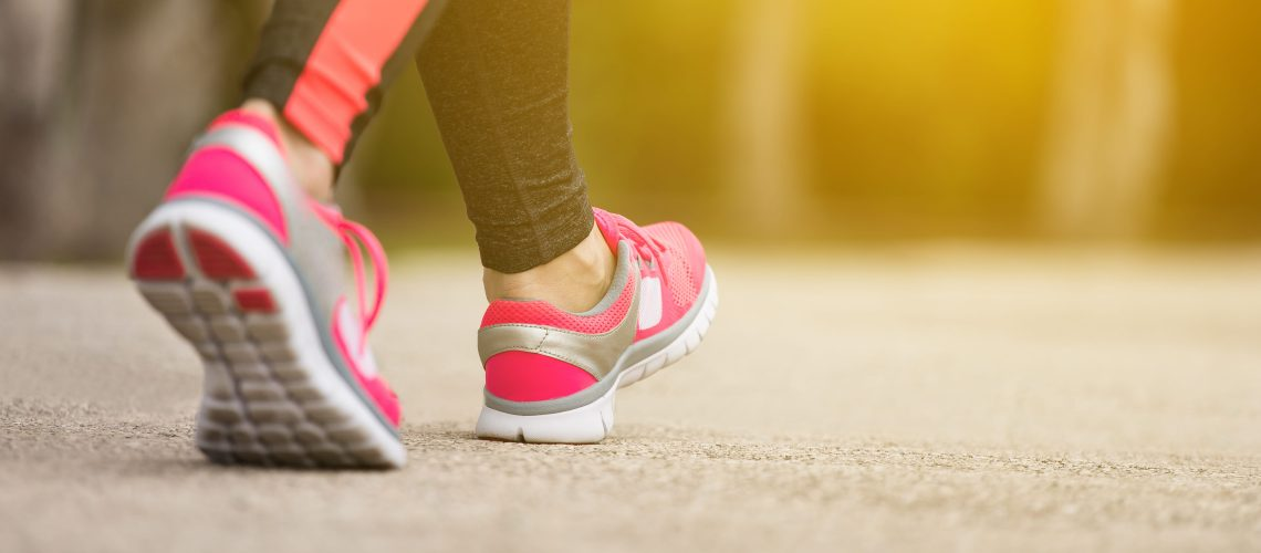 Fitness woman training and jogging in summer park, close up on running shoes in sunlight. Healthy lifestyle and sport concept