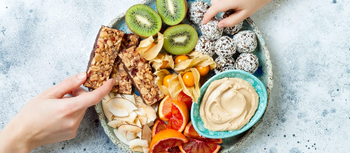 Mother sharing healthy vegan dessert snacks with toddler child. Concept of healthy sweets for children. Protein granola bars, homemade raw energy balls, cashew butter, toasted coconut chips, fruits platter
