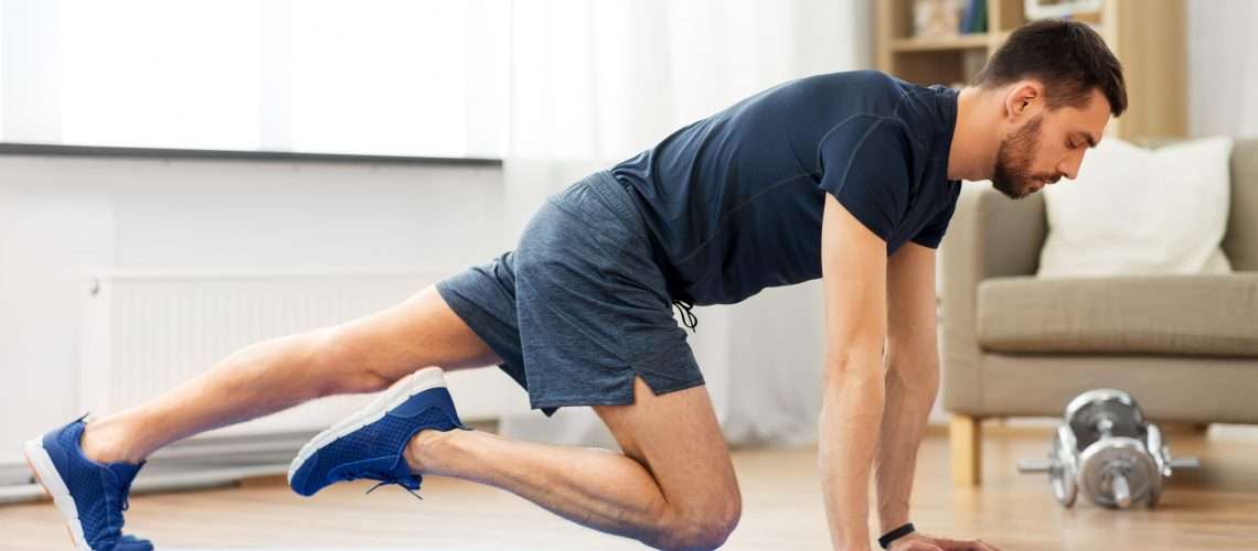 sport, fitness and healthy lifestyle concept - man with tablet computer doing running plank exercise at home