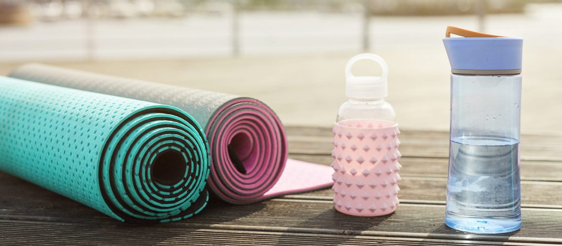 Background image of yoga mats and water bottles set for workout on wooden pier outdoors, copy space
