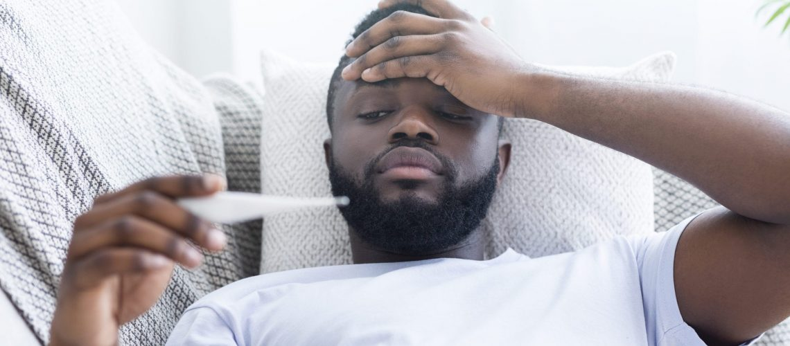 Must be sick. Sad african-american guy with fever measuring his body temperature, lying on couch at home