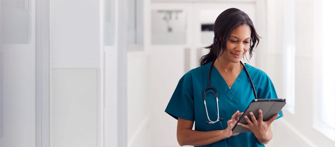 Female Doctor Wearing Scrubs In Hospital Corridor Using Digital Tablet