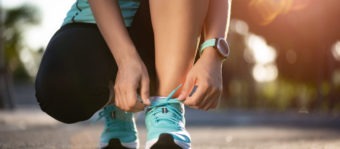Running shoes - closeup of woman tying shoe laces. Female sport fitness runner getting ready for jogging in garden background.
