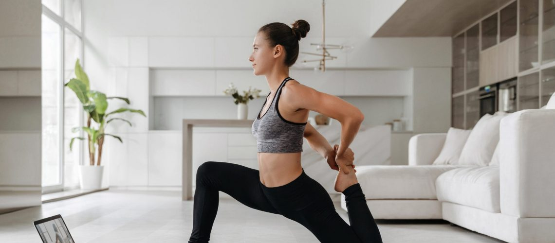 Full length shot of fit energetic young woman training at home because of social distancing, practicing yoga on mat, has virtual workout class, stretching. Online fitness, wellness and health concept