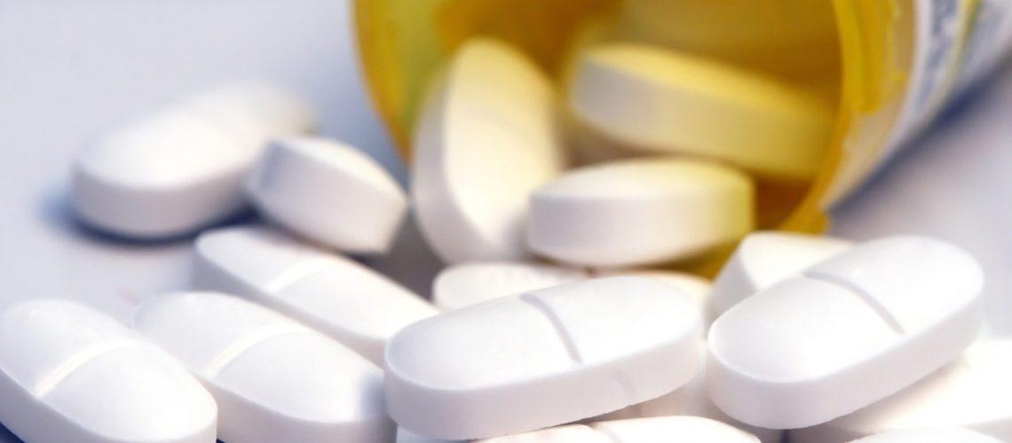 Open bottle of pills spilling onto the counter